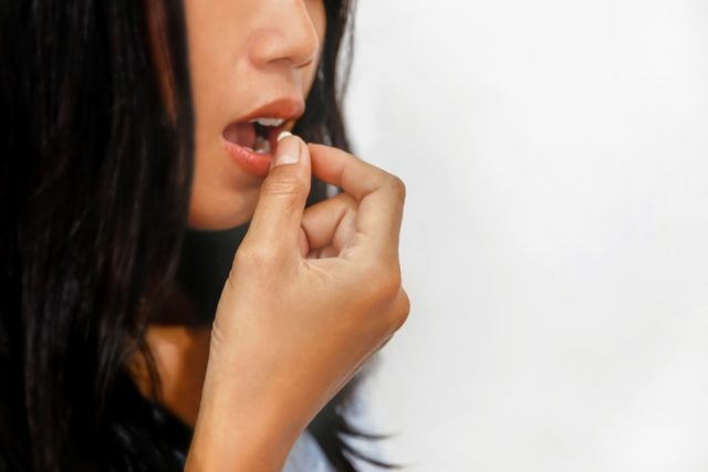 Woman about to swallow a pill.
