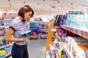 Woman confused looking at feminine hygiene products in a store.