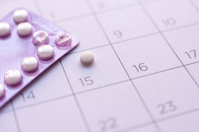 Birth control pill package on top of calendar. One pill placed on day 15.